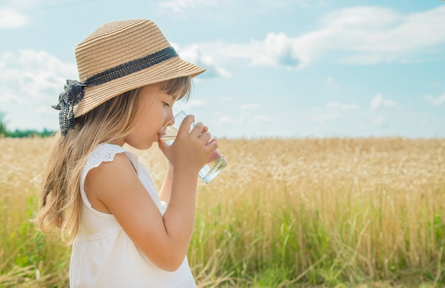 A child drinks water on the background of the field