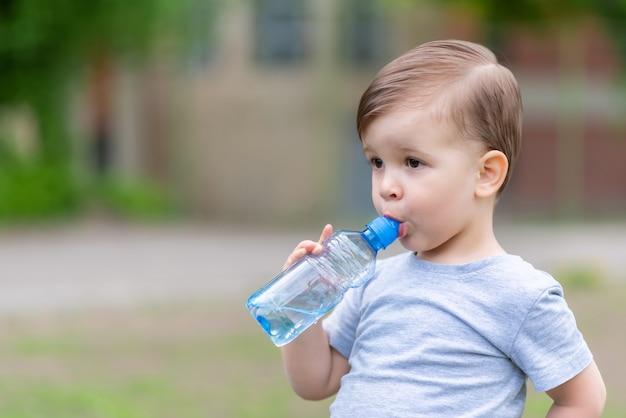 Ребенок пьет воду из бутылки в жаркий летний день
