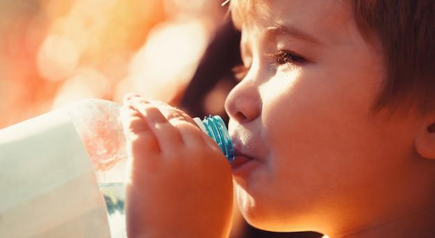 子供は歩きながらボトルから水を飲む、赤ちゃんの健康。水の男の子のボトル。飲み物の淡水ボトルを保持している少年。