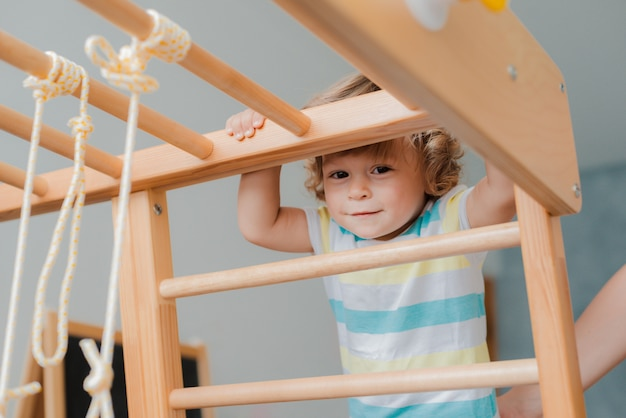 Child at an early age of 1.5 years is engaged in the home children's wooden sports complex.