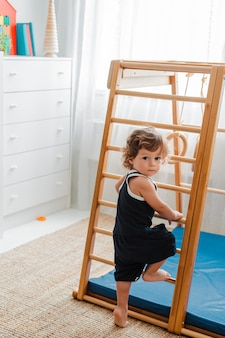 Child at an early age  is engaged in the home children's wooden sports complex.