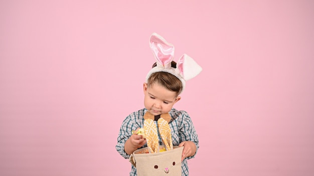 Child and easter, on pink background. high quality photo