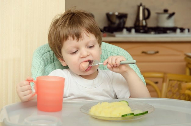 The child eat mashed potatoes, cucumber and sausages for dinner sitting in his children's chair in the kitchen.