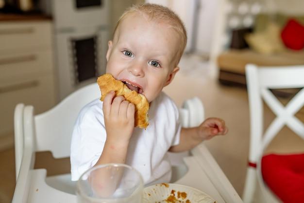 Ребенок ест вкусную домашнюю булочку, сидя в детском стульчике на кухне