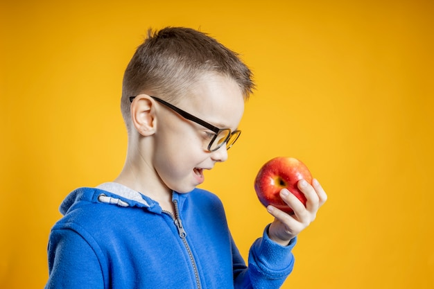 Child eating an apple on a yellow background