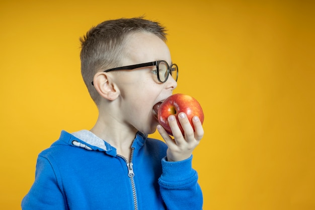Child eating an apple on a yellow wall