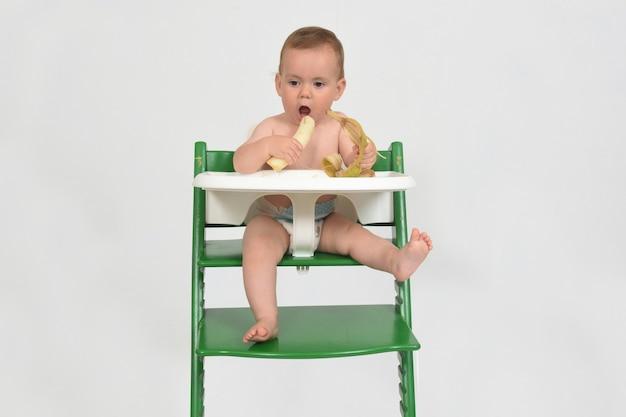 Ребенок ест банан и сидит в детском стульчике на белом фоне