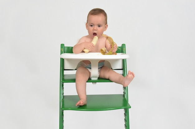 Child eating banana and sitting in a highchair on white background