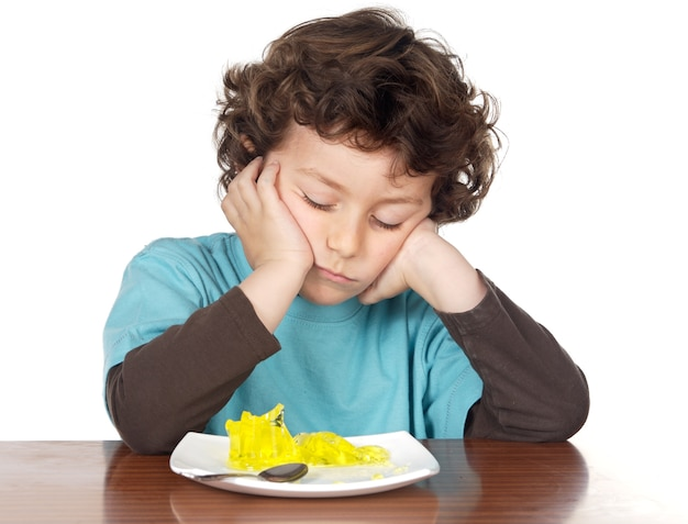 Child eating boring food over white background