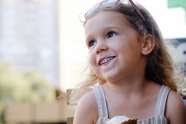 カフェ冷凍夏の食べ物の近くの外でコーンアイスクリームを食べる子供