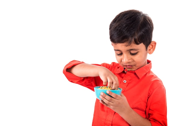 Child eating delicious noodle, indian kid eating noodles with fork on white wall