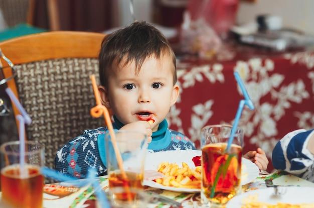 青いセーターで熱心に誕生日パーティーで手でフライドポテトを食べる子供
