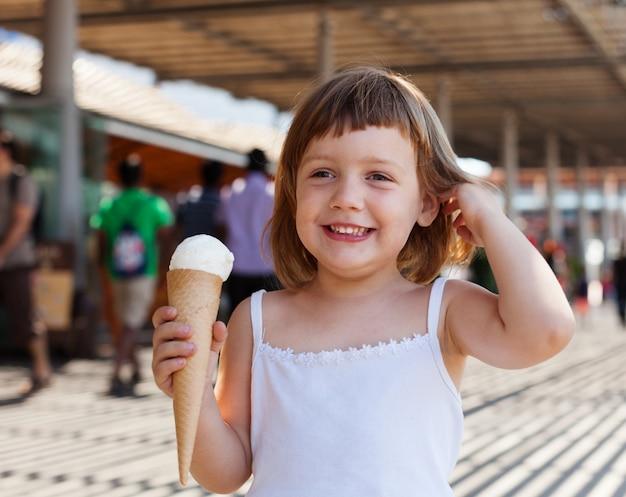 Ребенок ест мороженое на улице