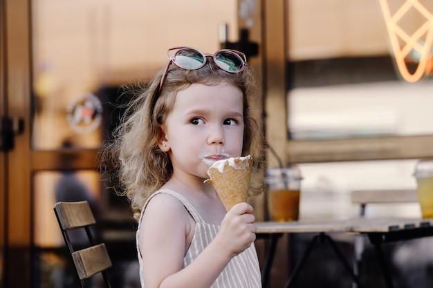 通りのカフェの近くでアイスクリームコーンを食べる子供 Premium写真