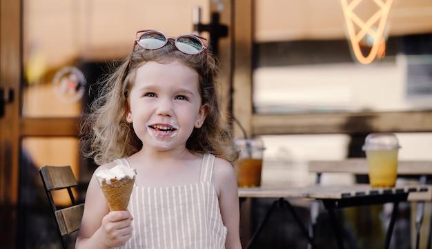 通りのカフェの近くでアイスクリームコーンを食べる子供