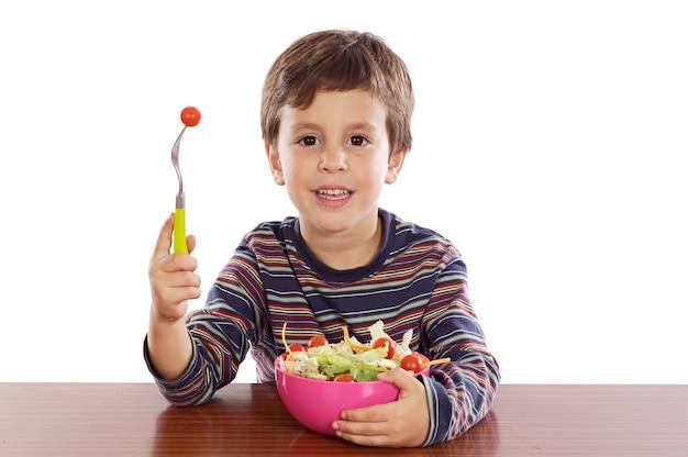 白い背景の上にサラダを食べる子供