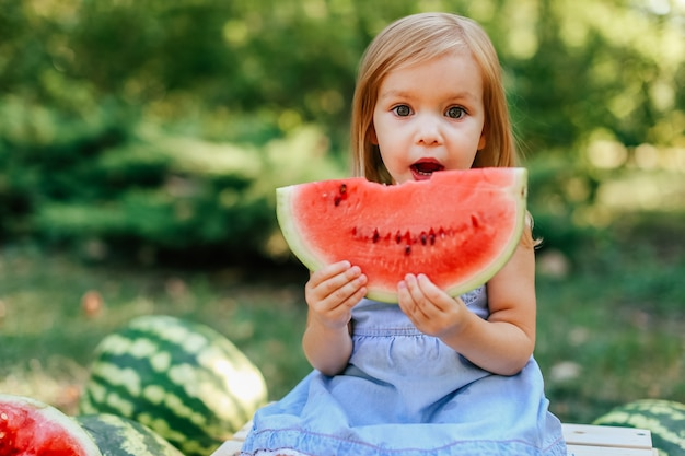 Child eating watermelon in the garden. kids eat fruit outdoors. healthy snack for children.