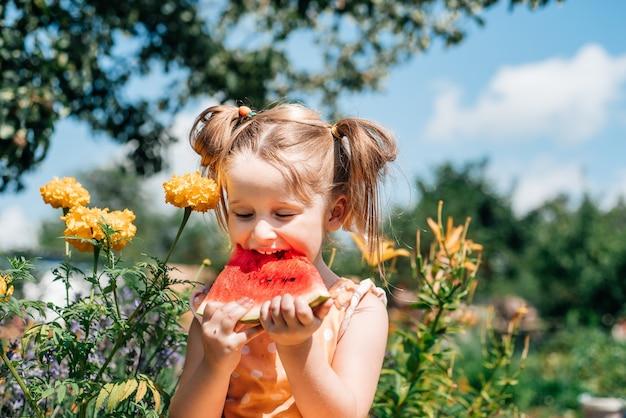 정원에서 수박을 먹는 아이. 아이들은 야외에서 과일을 먹습니다. 건강한 간식