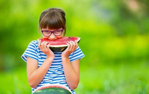 수박을 먹는 아이. 아이들은 정원에서 과일을 먹습니다. 물 멜론 조각을 들고 정원에서 사전 십 대 소녀. 수박을 먹는 행복한 여자 아이. 가스와 치아 교정기를 가진 여자 아이입니다.