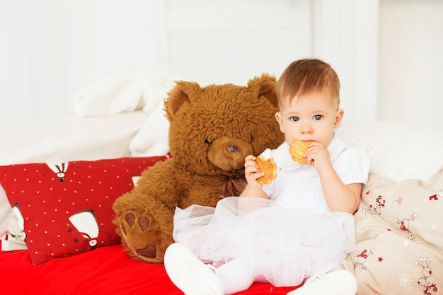 Child eats cookies. portrait of a beautiful baby girl with a soft brown teddy bear in the interior with christmas decorations.