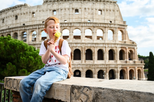 A child eats ice cream on the colosseum. italy, rome