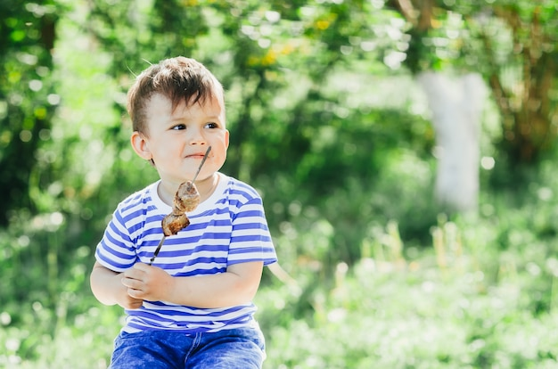 A child eats a kebab on a skewer, in a park or forest nature green background of trees and grass