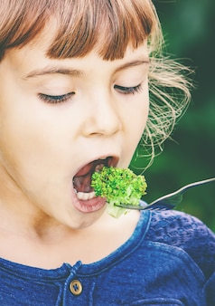 Child eats vegetables. summer photo. selective focus