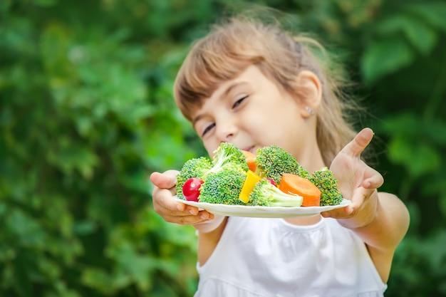 Child eats vegetables.