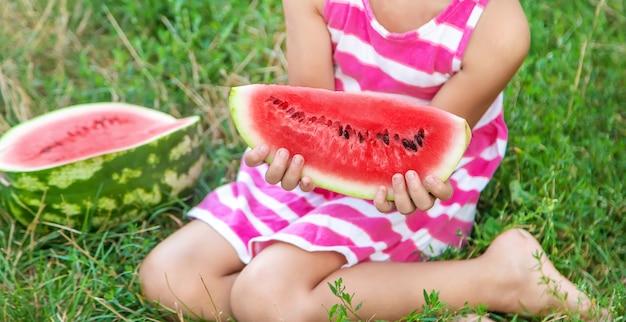 Child eats a watermelon in the garden