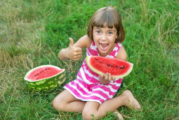Child eats a watermelon in the garden
