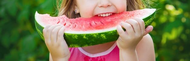 A child eats watermelon. photo. food.