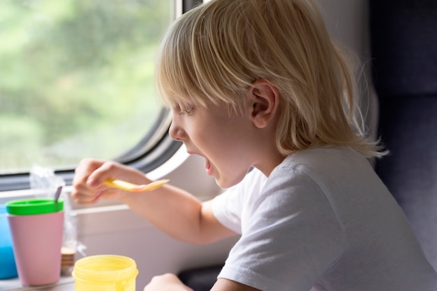 子供は客車に座って食事をします。鉄道で旅行します。