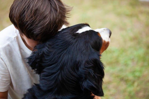 Child embraces his dog resting his head as a sign of affection and comfort.