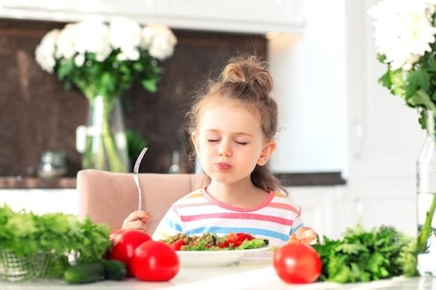 아이는 하얀 햇볕이 잘 드는 주방에서 건강한 샐러드를 먹는 것을 즐깁니다. 신선한 야채 영양 채식주의 개념 아이