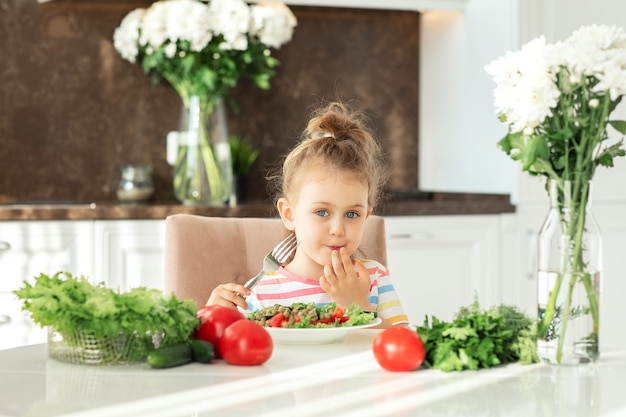 아이는 하얀 햇살 가득한 주방에서 건강한 샐러드를 먹는 것을 즐깁니다. 신선한 야채 영양 채식주의 개념