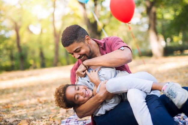 父親が彼女をくすぐっている間、子供は楽しんで笑います