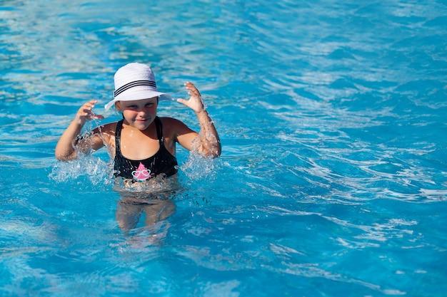 Ребенок наслаждается отдыхом в бассейне маленькая счастливая загорелая девочка в черном купальнике стоит в воде и х ...