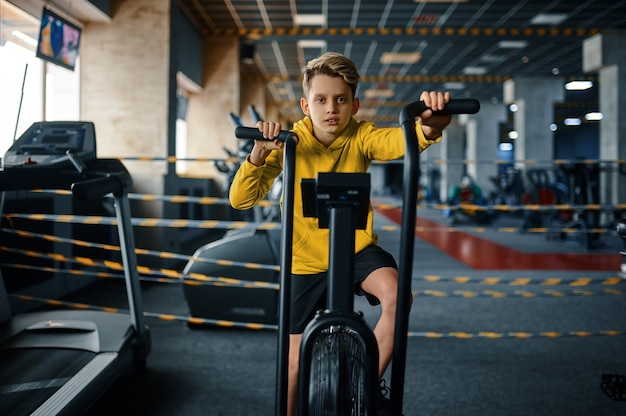 Child on exercise machine, side view, training in gym. youngster in sport club, healthcare and healthy lifestyle, schoolboy on workout, sportive youth