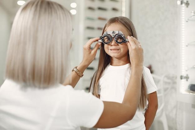 Проверка зрения у ребенка и проверка зрения. маленькая девочка, проверяющая глаза, с фороптером. врач выполняет проверку зрения для ребенка