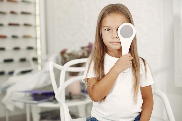 Проверка зрения у ребенка и проверка зрения. маленькая девочка, проверяющая глаза, с фороптером. проверка зрения для детей