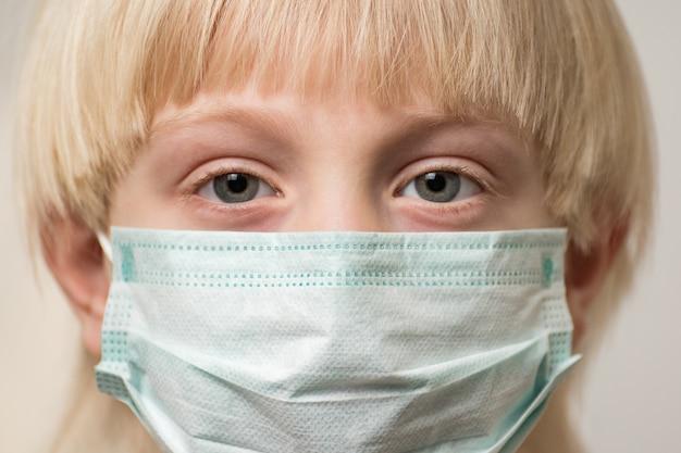医療マスクで子供の顔をクローズアップ。少年は使い捨てのサージカルマスクを着ています。