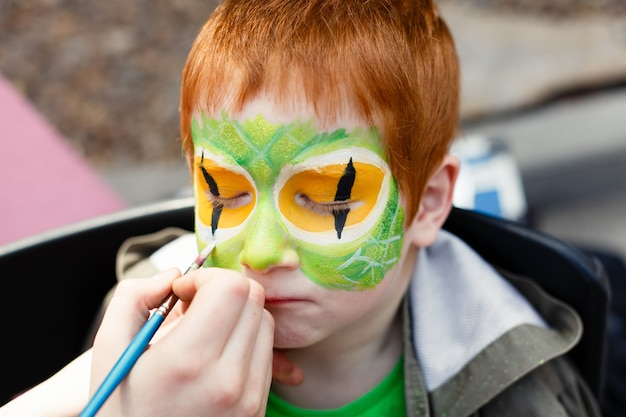 Child face painting process on redhead boy
