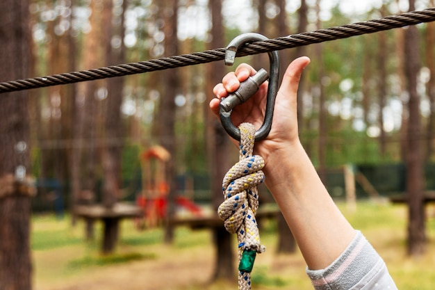 A child fastens a carbine on a safety rope