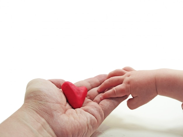 Child and father hand with heart made from play clay