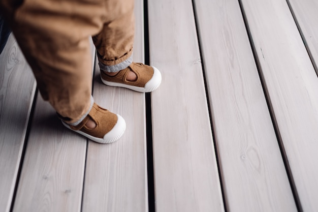 Child feet in boots standing on white surface like wooden deck