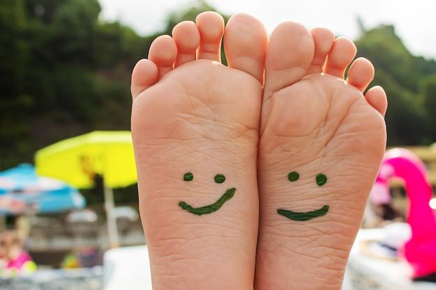 Детские ножки нарисованы красками на море. выборочный фокус.