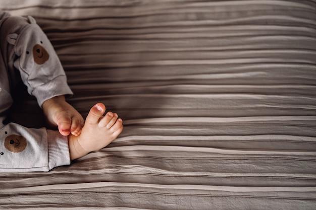 Child feet on striped fabrics surface like stylish brown blanket