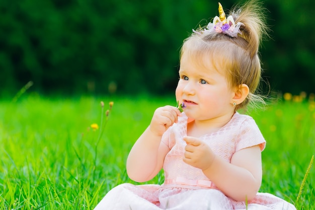 A child in a festive dress sitting on the grass in the park holding a small flower in her hands