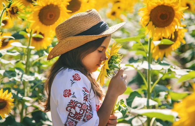 A child in a field of sunflowers in an embroidered shirt. ukraine independence day concept. selective focus.