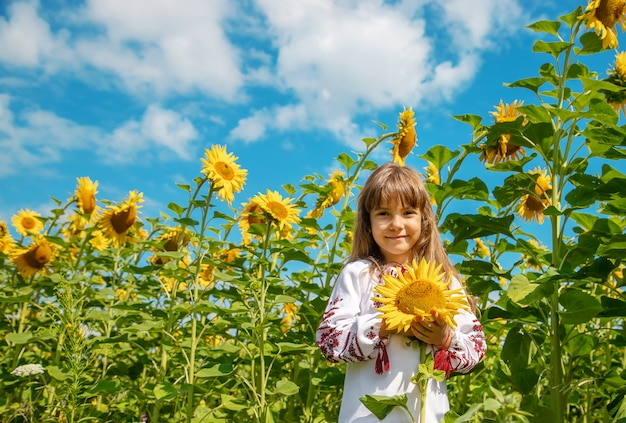 A child in a field of sunflowers in an embroidered shirt.